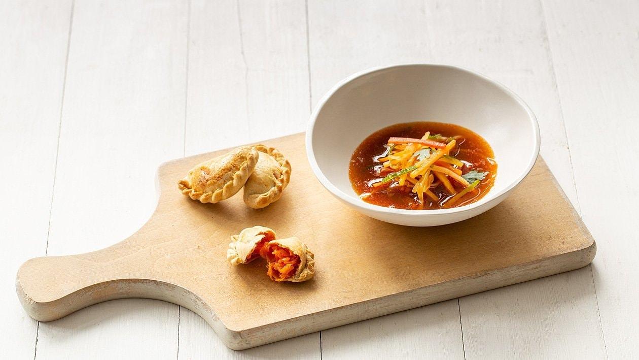 Krautsuppe mit Tomaten und mit Gemüse gefüllten Empanadas
