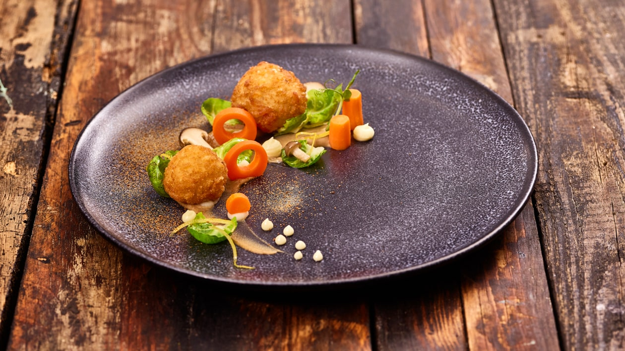 Vegane Steinpilz Arancini mit Pilzpüree und Kohlsprossen Salat